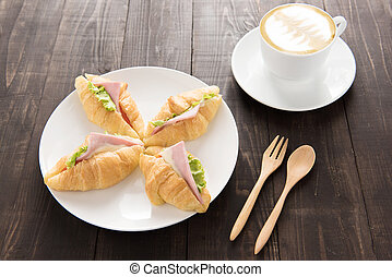 Croissant with parma ham and coffee on wooden table