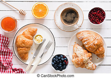 Croissants, coffee, jam and fruits. Continental breakfast table top view