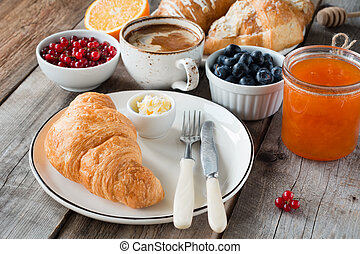 Croissants with coffee, butter, jam and fresh fruits