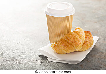 Croissants with coffee to go in a paper cup, take away...