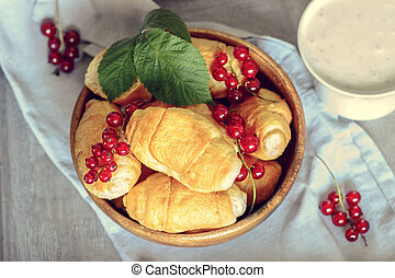 Croissants with currant berries on a wooden tray. The concept of a wholesome breakfast.