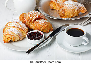 Croissants with jam and coffee on wooden table still life