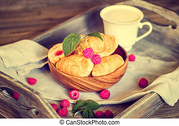 Croissants with raspberries on a wooden tray. The concept of a wholesome breakfast.