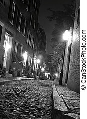 black and white image of an old 19th Century cobble stone road in Boston Massachusetts, lit only by the gas lamps revealing the shuttered windows and brightly lit doorways of the rowhouses on Acorn Street