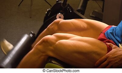 Crop athlete doing leg exercise on machine - Crop sportsman...