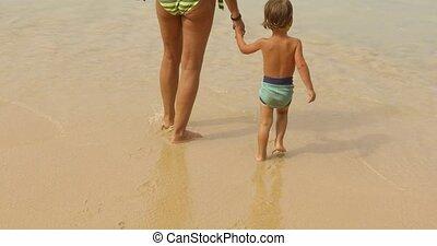 Crop boy with parent walking on beach