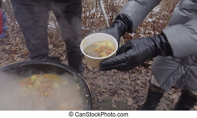 Crop cook serving stew to people in countryside