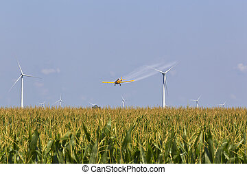 Crop Duster - A agricultural plane dusts crops against a...
