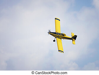 Crop Duster - Yellow crop duster flying against a cloudy...