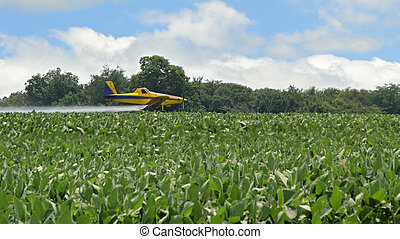 Airplane spraying insecticides onto a soybean farm field
