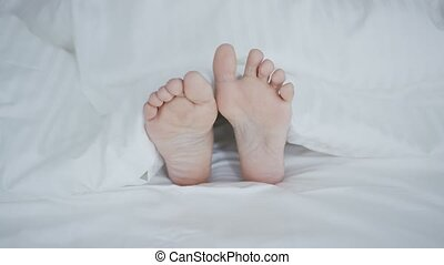 Crop female feet under blanket - Crop shot of woman lying...