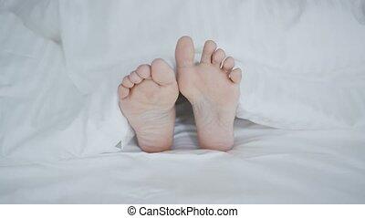 Crop female feet under blanket - Crop shot of woman lying...