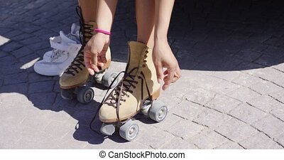 Crop female putting on roller skates - Crop shot of female ...