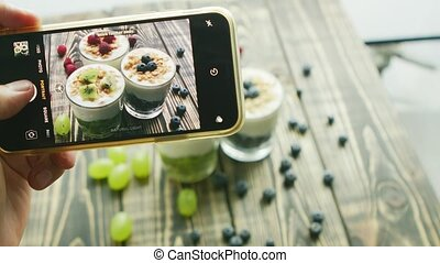 Crop hand taking photo of fresh desserts - Hand of...