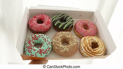 Crop hand with box of donuts - Crop hand holding open box...