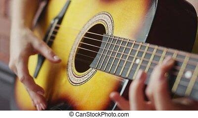 Crop hands playing guitar
