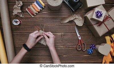 Crop hands wrapping present with string