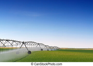Crop Irrigation - A farm being irrigated with a center pivot...