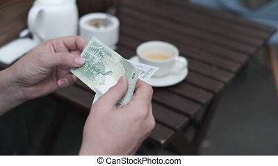Anonymous male sitting at table in cafeteria and counting cash while getting ready for payment, Qatar banknotes