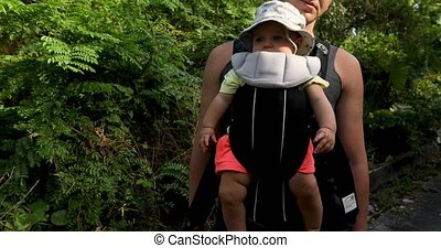 Crop man with baby in carrier - Crop side view of man stands...