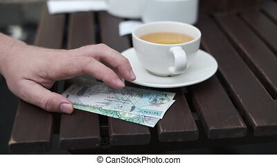 Closeup of anonymous male customer sitting in patio of cafe and tapping with finger on table with cash while waiting for bill, kuwaiti, note, arab, dinar,, Qatar