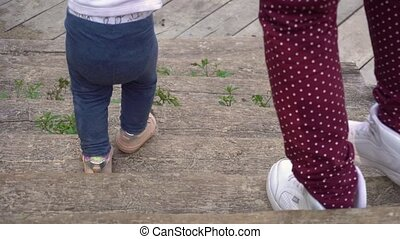 Crop mother and daughter walking down steps - Crop legs of...