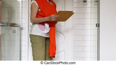 Crop mother holding baby in sling working on tablet - Young...