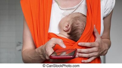 Crop mother with baby in sling holding smartphone -...