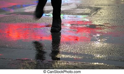 Crop of man stepping in puddle on street - Crop shot of man...