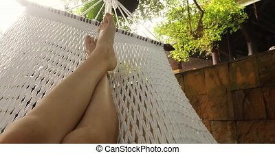 Crop person chilling in hammock - Crop shot of barefoot feet...