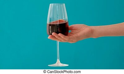 Anonymous person carrying glass goblet of fine red wine against bright blue background