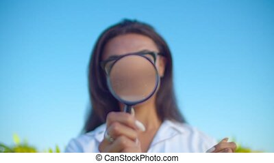Crop scientist looking through magnifier in nature - ...