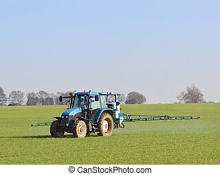 an english landscape with a blue tractor mounted sprayer working on a winter wheat crop on a fine day in february
