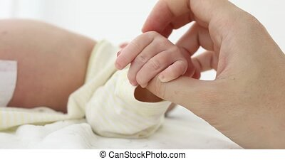Crop tender hand holding tiny newborn hand - Close-up shot...