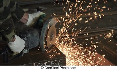 Crop unrecognizable worker cutting metal with angle grinder...