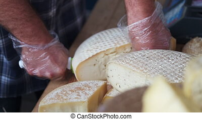 Faceless seller in gloves cutting piece of cheese head and weighing while working at stall on market