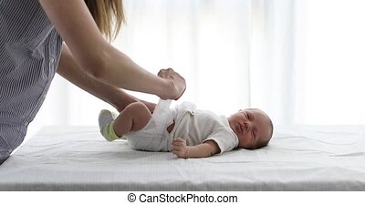 Crop woman changing diaper of baby