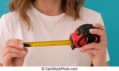 Woman shows small size and enlarges it to a larger. Female in white t shirt unrolling construction measuring tape against blue background
