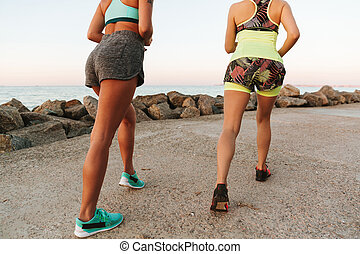 Cropped back view image of two women preparing to run