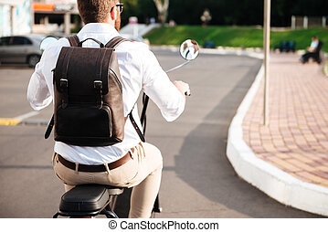Cropped back view of man with backpack rides on motorbike