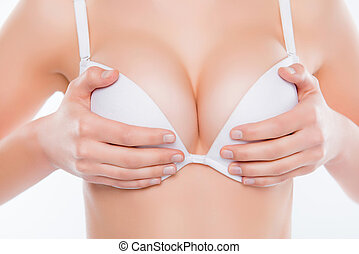 Cropped close up photo of big ideal perfect beautiful sexy stunning gorgeous symmetric erotic woman's breast, hands holding bra cups isolated on white background, wellbeing, wellness concept