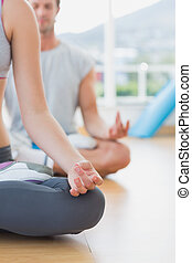 Cropped couple in meditation pose at fitness studio -...