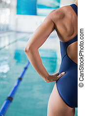 Cropped female swimmer by pool at leisure center