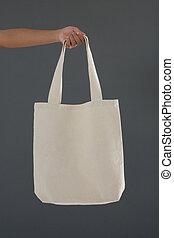 Cropped hand of female customer holding shoulder bag
