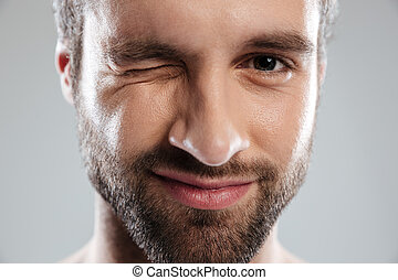 Cropped image of a bearded mans face winking
