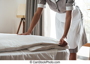 Cropped image of a chambermaid making bed in hotel room - ...