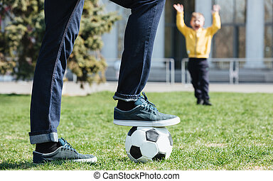 Cropped image of a father playing football with his son