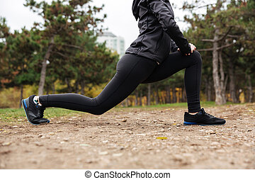 Cropped image of a fitness girl stretching legs