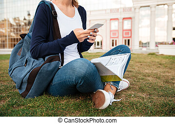 Cropped image of a girl student with backpack studying