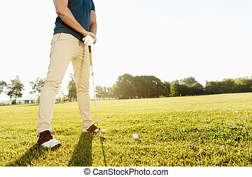 Cropped image of a golfer getting ready